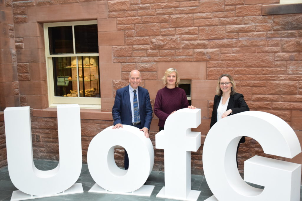 Professor David Clark, Dr Marian Krawczyk, and Dr Naomi Richards standing together in the foyer of Rutherford McCowan, next to the large U of G letters
