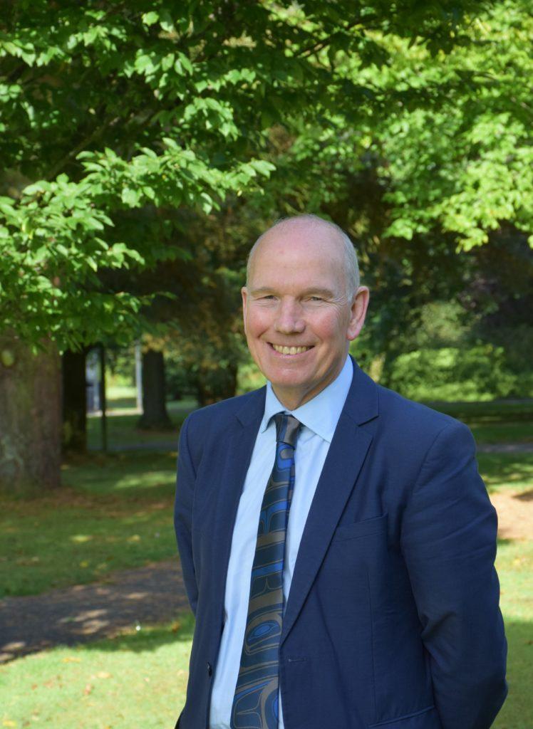 Professor David Clark standing with trees